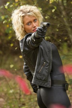 ljuddämparen: Sexig kvinna med en ljuddämpare pistol syftar i kameran - utomhus Stockfoto