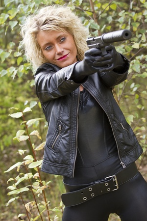 Female killer with a silencer gun smiling and aiming photo