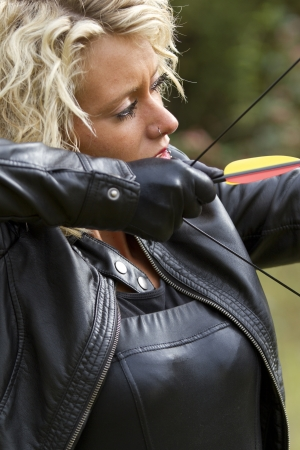 Woman clad in leather outfit shooting with bow and arrow photo