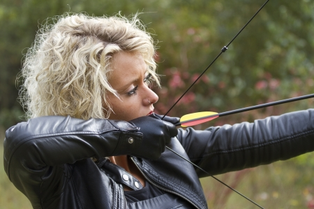 female assassin: Woman shooting with bow and arrow outdoor
