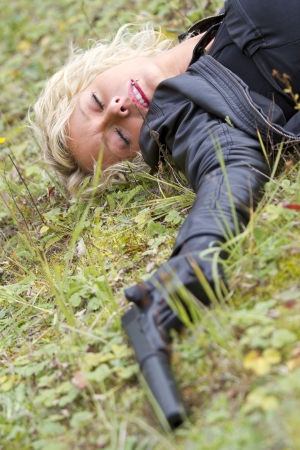 Crime scene - woman playing dead scene with a silencer handgun in her hand, focus on the face