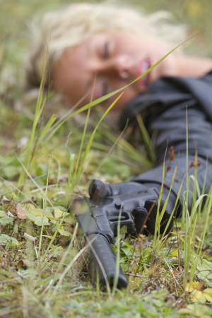 Crime scene - woman playing dead scene with a silencer handgun in her hand, focus on the gun photo
