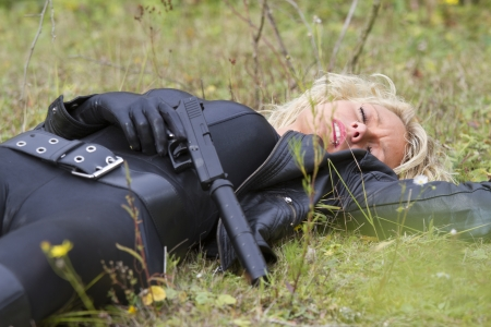 silencer: Crime scene - woman shot down, playing dead scene with a silencer handgun in her hand, lying on the ground outdoor
