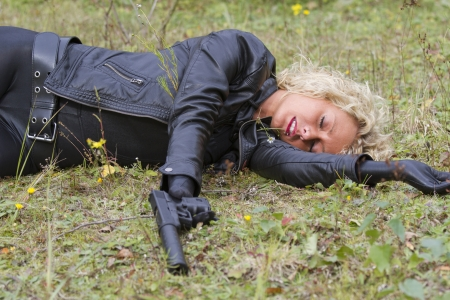 Crime scene - woman playing dead scene with a silencer handgun in her hand, lying on the ground outdoor