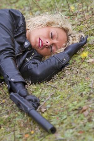 vermoord: Crime scene - vrouw spelen dood scène met een geluiddemper pistool in haar hand, liggend op de grond buiten