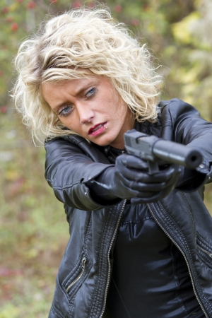 ljuddämparen: Kvinna siktar med ljuddämpare pistol utomhus Stockfoto