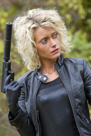 catsuit: Woman in leather jacket holding a silencer handgun, looking at the side