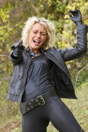 catsuit: Angry and screaming woman shooting from her silencer handgun outdoor Stock Photo