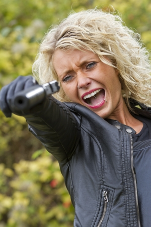 Screaming woman shooting from silencer handgun outdoor photo