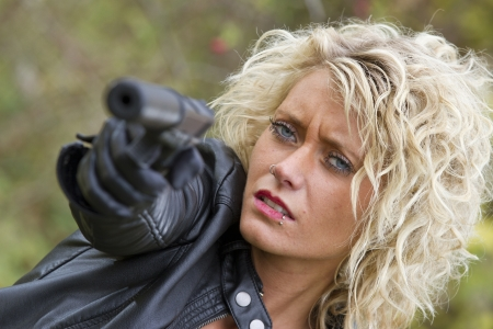 the silencer: Close up Portrait of woman with a silencer gun shooting Stock Photo