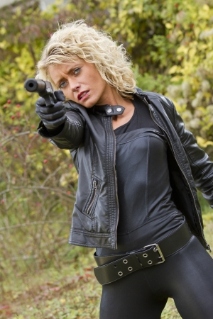 catsuit: Sexy female spy shooting from her silencer handgun - outdoor Stock Photo