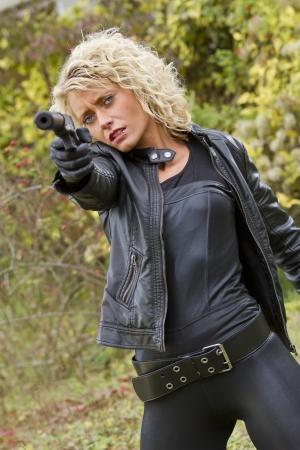Sexy female spy shooting from her silencer handgun - outdoor Stock Photo - 15981549