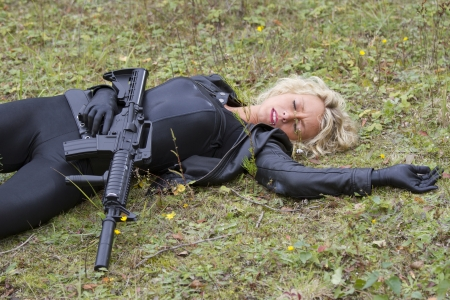 catsuit: Woman playing dead scene with machine gun - killed in action Stock Photo