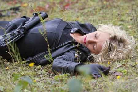 war crimes: Woman playing dead scene with machine gun - killed in action Stock Photo