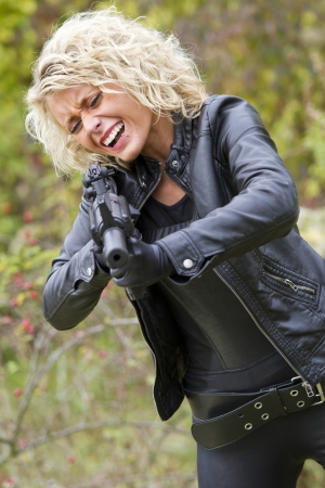 catsuit: Screaming woman shooting from machine gun with silencer outdoor Stock Photo