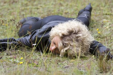 vermoord: Crime scene - vrouw spelen dood scène met een machinegeweer in haar hand, liggend op de grond buiten