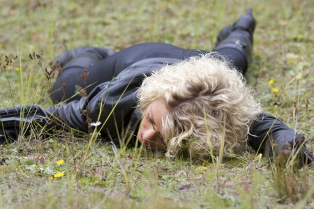 war crimes: Crime scene - woman playing dead scene with a machine gun in her hand, lying on the ground outdoor Stock Photo