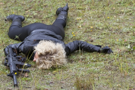 Crime scene - woman shot down, playing a dead scene with machine gun in her hand, lying on the ground photo
