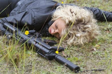 Crime scene - woman playing dead scene with machine gun in her hand