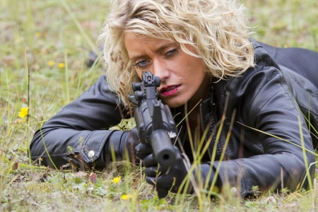 silencer: Female killer aiming with a machine gun, lying on the ground Stock Photo