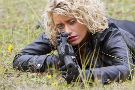 ljuddämparen: Kvinna mördare siktar med ett maskingevär, liggande på marken Stockfoto