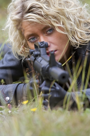 the silencer: woman in leather outfit with machine gun lying in grass and aiming