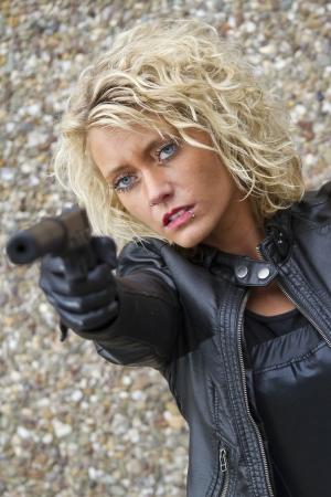 Female assassin with a silencer handgun menacing someone Stock Photo