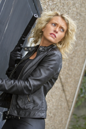 ljuddämparen: Kvinna mördare, mördare stående vid dörren med en ljuddämpare pistol, titta på sidan