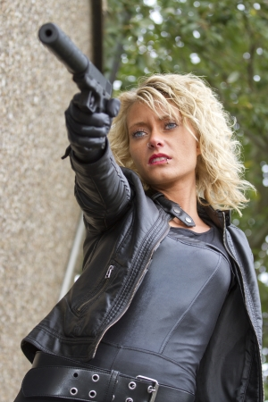 ljuddämparen: Assassin klädda i läder klädsel siktar med ljuddämpare pistol utomhus Stockfoto