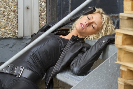Crime scene - woman playing dead scene with a silencer handgun in her hand, lying on stairs Stock Photo