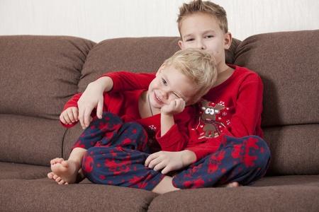 mann couch: Zwei gl�ckliche Jungen sitzen auf dem Sofa Lizenzfreie Bilder