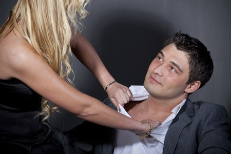 ripping shirt: Passionate couple over grey background in studio Stock Photo