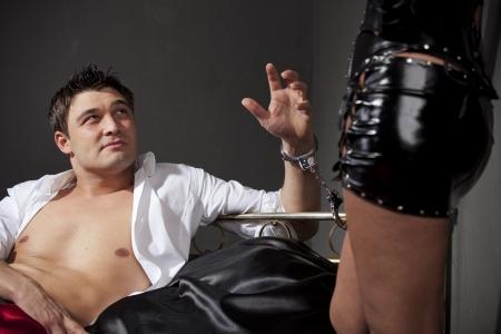 herrin: Man auf dem Bett während der sexuellen Spiele mit Handschellen