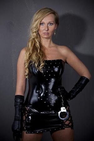 dominacion: Dominatrix - mujer en traje de cuero de pie en la pared Foto de archivo