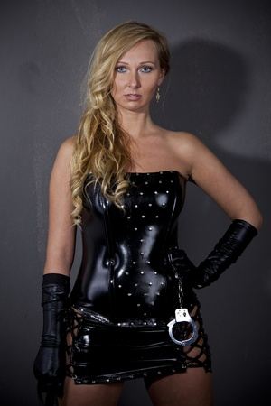 domination: Dominatrix - Woman in leather outfit standing at the wall
