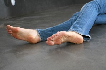 female soles: crime scene - limp woman on the ground - female feet in focus