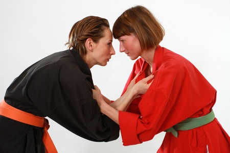 female wrestling: two women in judo kimonos in fighting stance over white background