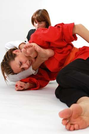 choking: women fighting martial arts over white background
