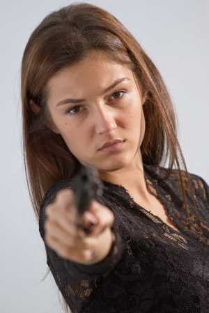 serious woman aiming with a handgun in the camera photo