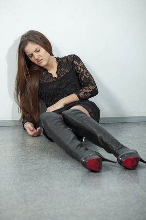 young woman in pain sitting on the floor, wearing over knee boots and mini dress photo