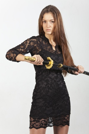 young woman in black dress posing with sword photo