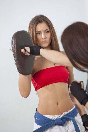 punching bag: women fitness punching training with boxing mitts  Stock Photo