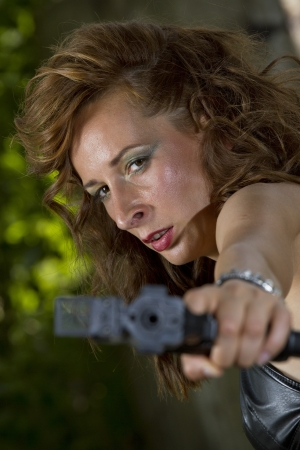Angry gun woman shooting from a handgun photo