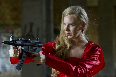Sexy female spy in red dress and raincoat holding machine gun - outdoor photo