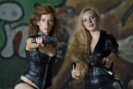 catsuit: Two leather clad gun women aiming in the camera