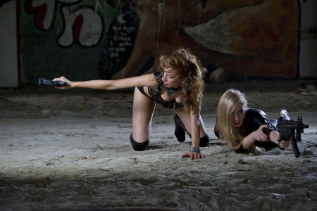 Two sexy female spies in leather outfits shooting from their guns photo