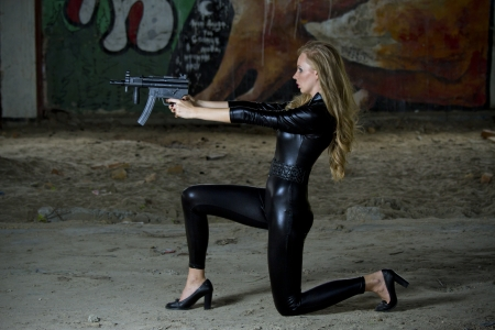 catsuit: Gun woman in leather catsuit shooting from machine gun Stock Photo