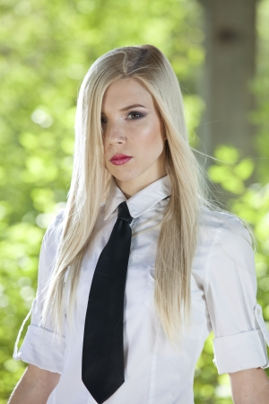 Portrait of young woman in white shirt and tie posing outdoor photo