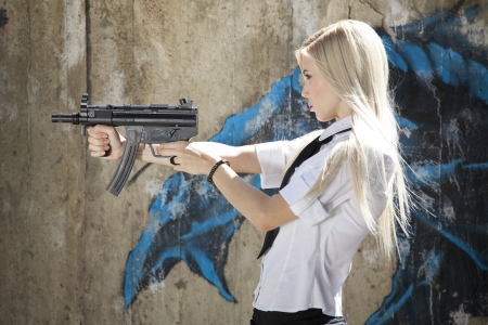 young female spy in white blouse and tie holding a automatic machine gun