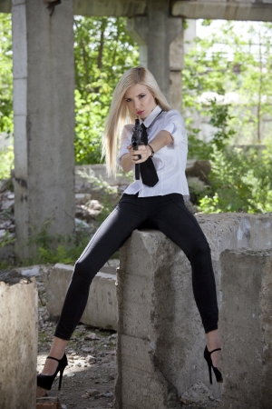 Woman in white shirt and tie holding a machine gun in old fabric ruins photo